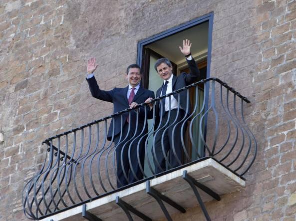 Ignazio Marino (a sinistra)  e Gianni Alemanno (a destra) salutano dal balconcino del Comune dopo la proclamazione e il passaggio di consegne  a giugno 2013 (Ansa)