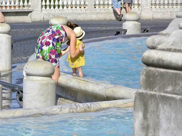 Una mamma immerge la piccola nella Fontanone del Gianicolo (LaPresse)