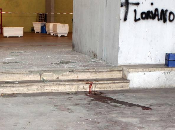Tracce di sangue all'entrata del palazzo da cui il ragazzo è caduto