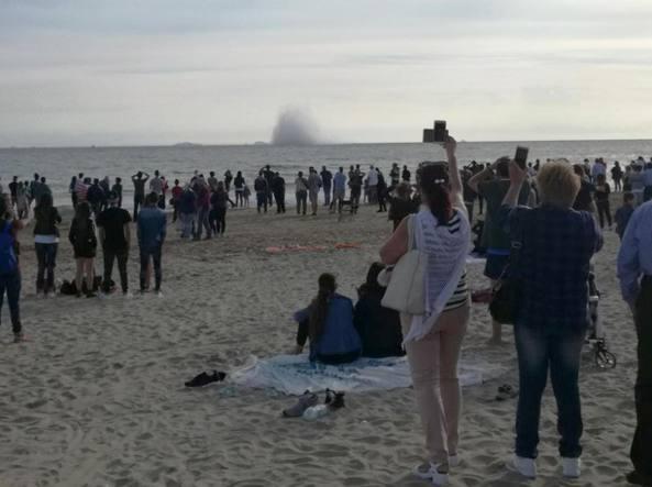 Spettatori sgomenti guardano il caccia precipitato in mare (Ansa)