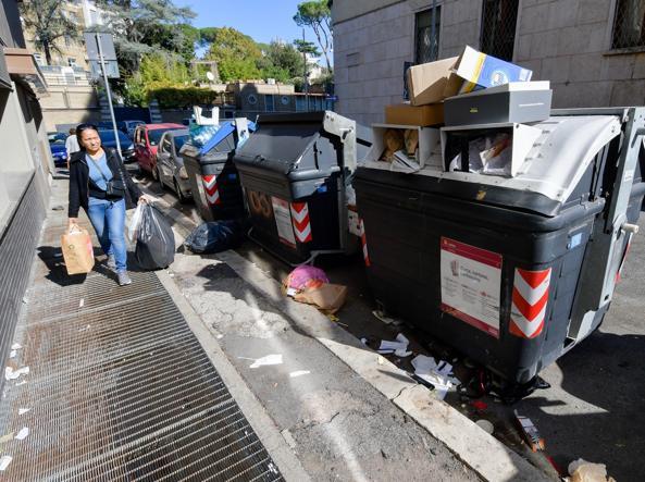 Cassonetti strapieni in via Lovanio (foto Lapresse)